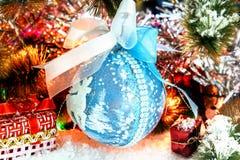 Presente do vermelho e bola do Natal na neve contra um fundo do ouropel brilhante Luzes de incandescência Bokeh Fotografia de Stock Royalty Free