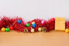 Presente dourado com a fita vermelha na tabela para o ano novo e o Natal Foto de Stock Royalty Free