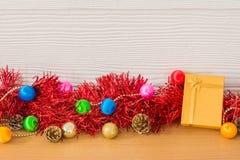 Presente dourado com a fita vermelha na tabela para o ano novo e o Natal Foto de Stock