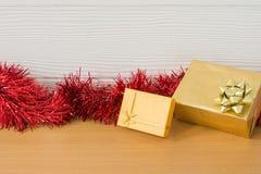 Presente dourado com a fita vermelha na tabela pelo ano novo Imagens de Stock Royalty Free
