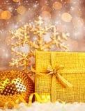 Presente dourado do Natal com decorações dos baubles Imagens de Stock Royalty Free