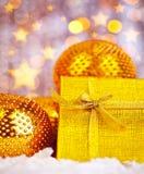 Presente dourado do Natal com decorações dos baubles Fotografia de Stock Royalty Free