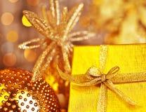 Presente dourado do Natal com decorações dos baubles Imagem de Stock
