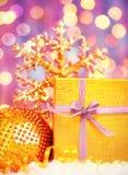 Presente dourado do Natal com decorações dos baubles Fotografia de Stock