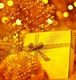 Presente dourado do Natal com decorações dos baubles Imagens de Stock