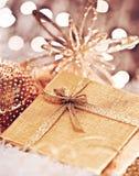 Presente dourado do Natal com decorações dos baubles Fotos de Stock Royalty Free