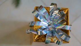 Presente dourado do Natal sob a árvore de Natal Caixa de presente do Natal com fitas agradáveis filme