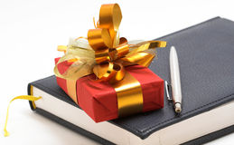 Presente e caderno vermelhos com pena Imagem de Stock Royalty Free