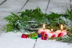 Presente e candele sul portico innevato Immagine Stock