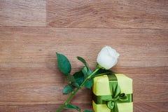 Presente e rosa do branco em um fundo de madeira Foto de Stock