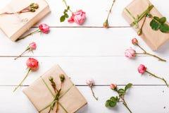 Presente e rosas no fundo branco de madeira workspace Vista superior, configuração lisa fotografia de stock royalty free