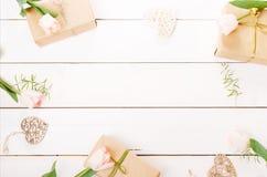 Presente e rosas no fundo branco de madeira workspace Vista superior, configuração lisa foto de stock royalty free