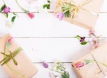 Presente e rosas no fundo branco de madeira workspace Vista superior, configuração lisa imagens de stock royalty free
