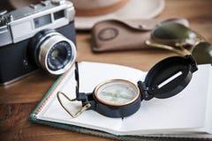Presente el cuaderno del whith, la cámara del vintage, el compás, las gafas de sol y el sombrero Imágenes de archivo libres de regalías