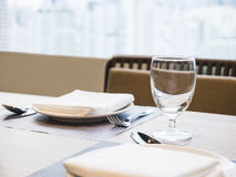 Presente el sistema de cena con la servilleta de la placa y el fondo del restaurante del vidrio Imagenes de archivo