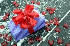Presente embalado enchido com os corações vermelhos e a neve branca imagem de stock royalty free