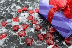 Presente embalado enchido com os corações vermelhos e a neve branca fotografia de stock