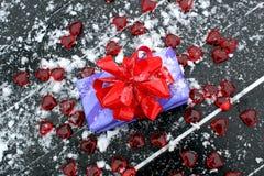 Presente embalado enchido com os corações vermelhos e a neve branca imagens de stock