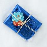 Presente empacotado com símbolos do Natal, fundo branco da neve foto de stock