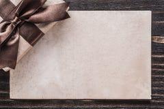 Presente encaixotado com papel amarrado da curva na placa de madeira do vintage imagens de stock