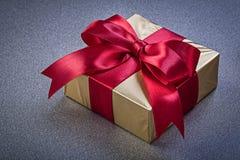 Presente encaixotado no papel glittery no conceito cinzento dos feriados do fundo fotografia de stock royalty free