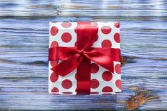 Presente encaixotado vermelho na placa de madeira do vintage foto de stock