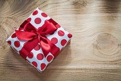 Presente encajonada con la cinta roja en concepto de los días de fiesta del tablero de madera imagenes de archivo