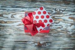 Presente encajonado rojo en el tablero de madera del vintage fotografía de archivo libre de regalías