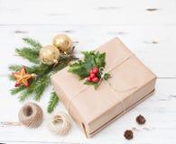 Presente envolvido no papel comum com um ramo da pele-árvore e as bolas do Natal Fotografia de Stock