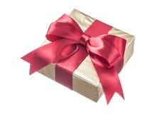 Presente envuelto en papel reluciente con la cinta roja aislada en wh Imagen de archivo