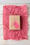 Presente envuelto llano en la tabla de madera del tejido Imagen de archivo
