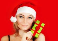 Presente feliz do Natal da terra arrendada da menina de Santa Foto de Stock