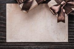 Presente inscatolati con la carta marrone legata dei nastri sul bordo di legno Fotografia Stock