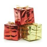 Presente luccicanti dell'oro e di rosso isolati su fondo bianco Immagine Stock