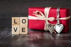 Presente na caixa vermelha, um pendente na forma de um coração em uma prata c Fotos de Stock Royalty Free
