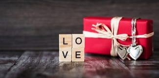 Presente na caixa vermelha, um pendente na forma de um coração em uma prata c Foto de Stock Royalty Free