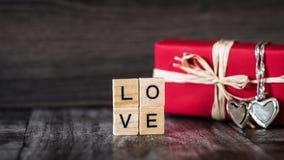Presente na caixa vermelha, um pendente na forma de um coração em uma prata c Imagem de Stock Royalty Free