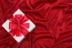 Presente na seda vermelha. Fotografia de Stock Royalty Free