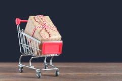 Presente no carrinho de compras em uma superfície de madeira Fotografia de Stock Royalty Free