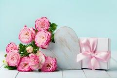 Presente ou caixa atual, flores cor-de-rosa e coração de madeira na tabela do vintage Cartão para o dia do aniversário, da mulher Foto de Stock