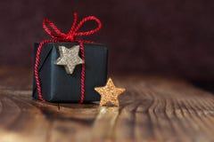 Presente para la Navidad con las estrellas de oro y de plata Imagenes de archivo