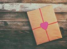 Presente para o papel de envolvimento do dia do ` s do Valentim amarrado com uma fita vermelha com um coração no fundo de madeira Imagens de Stock Royalty Free