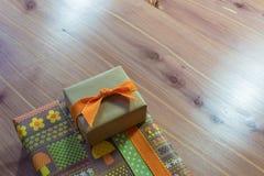 Presente pequeno empilhado em um presente maior, em uma diagonal, em uma fita alaranjada no marrom e em uns papéis de envolviment fotografia de stock