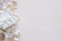 Presente, perle, conchiglie, orchidea e spazio per testo su fondo di legno Fotografie Stock Libere da Diritti