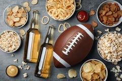 Presente por completo de los bocados y de la cerveza preparados para mirar el fútbol americano en la TV, visión superior imagen de archivo