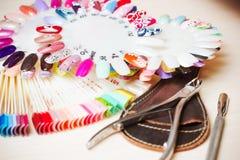 Presente por completo de los utensilios de la manicura, herramientas de la manicura, colores del esmalte de uñas en la paleta Cla Fotografía de archivo