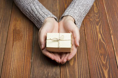 Presente, regalo Ciérrese para arriba de las manos femeninas que sostienen el pequeño regalo foto de archivo libre de regalías