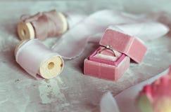 Presente romântico: caixa cor-de-rosa de veludo com as fitas do cetim de uma aliança de casamento e da luz em um fundo cinzento foto de stock royalty free