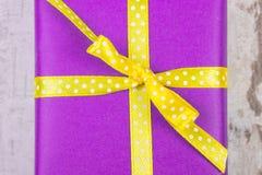 Presente roxo para o Natal ou a outra celebração na prancha de madeira Fotos de Stock