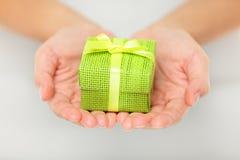 Presente verde colorido nas mãos colocadas fotografia de stock royalty free